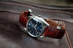 Help me recreate this style: Blue faced Omega watch with red leather band.