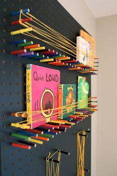 Hang a pegboard and use cut down colored pencils and rubber bands or string as multi-purpose shelving and art board.