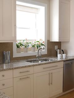 Upping the Ante An undermount sink, pullout faucet, and oversize cabinet hardware are upscale touches. The contemporary backsplash in the kitchen's work zone features hand-chopped glass tiles with coordinating grout.