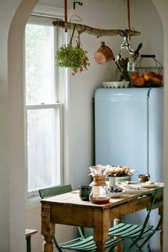 Love the dried herbs and glass vase hanging on the wood piece, above the table