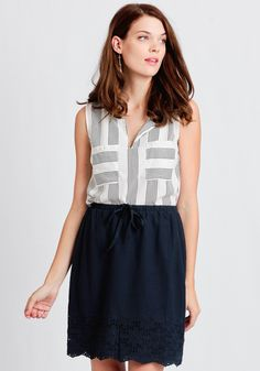 This navy cotton skirt is designed with an elastic waistband with a self-tie drawstring closure and a modest silhouette.
