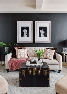 """The little living room area, including some commissioned black and white photos. """"Is that you in the black and white photos?"""" is what friends ask Angie. But they're not of her! """"I had the photos commissioned by a local photographer using a model but I never imagined people might think it was actually me! They're definitely a conversation piece!"""" Angie's favorite piece in the whole apartment is the steamer trunk."""