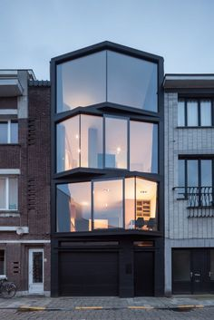 Located in an upcoming neighbourhood in Ghent, Belgium, the compact family home was designed by architects Steven Vandenborre and MiASS Architectuur and is conceived as a stack of three angular glass volumes, sitting on top of a solid base.