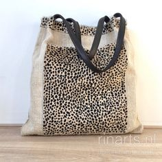 Tote bag made from an antique grain sack with a cheetah print hair on hide trim and front pocket