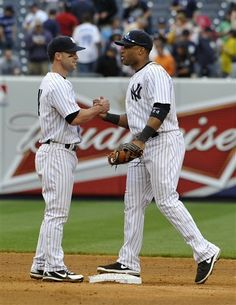 New York Yankees third baseman Jayson Nix, left, congratulates second baseman Robinson Cano after the Yankees beat the Toronto Blue Jays 7-2 in a baseball game at Yankee Stadium on Saturday, May 18, 2013 in New York. Cano hit two two-run home runs in the game.