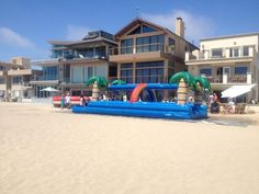 Dual Slip and Slide inflatable water slide setup at Santa Monica Beach. We do beach events with inflatables, slides, and bounce houses at Los Angeles and Orange County beaches. Call  800 873-8989 to rent.