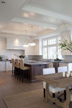 Open kitchen design with white shaker cabinets, cherry kitchen island, concrete countertops, marble subway tiles backsplash, seagrass bar stools, jute rug, trestle dining table and white dining chairs. By Milton Development.