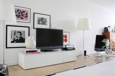 Hang large pics low.  Draw attention away from your TV by echoing its size and shape with artwork. Hang artwork above, to each side and slightly behind the TV. This display idea would work equally well opposite a low seating area, with or without the media center.