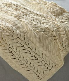 Free Knitting Pattern for Classic Lace Baby Throw - This baby blanket by Lion Brand Yarn is knit in 3 panels of lace and 2 panels of seed stitch and then seamed. 32 x 35 in. (81.5 x 89 cm)