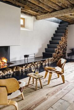 Rustic wood flooring with feature fireplace and log storage. Rustic timber ceiling