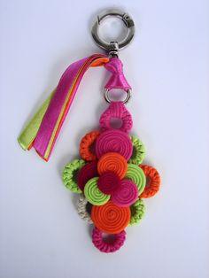 A base do chaveiro é de argolas com  crochê de  tiras de malha, uma argola cromada, um mosquetão, fitas de cetim e um compôse de rolinhos .          Podemos fazer a combinação de cor que você desejar....