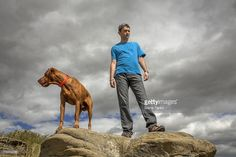 Image result for man standing on cliff with dog