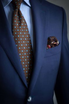 Navy suit paired with a soft blue shirt. The blue dots in the brown tie make for…