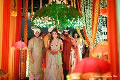 Harleen enters her sangeet ceremony under a floral umbrella