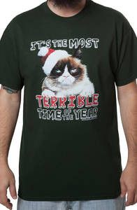 "This Grumpy Cat t-shirt shows the miserable kitty wearing a Santa Hat with his Grumpy Expression on his face. The shirt reads ""IT'S THE MOST TERRIBLE TIME OF THE YEAR""."