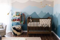 """An Alaskan Babymoon Inspires a Beautiful Blue NurseryAs one commenter complimented Colton's Alaska-inspired nursery, """"It's just """"themey"""" enough -- nature, animals, wool and wood."""" The mountain ranges on the walls were hand-painted by Colton's mom, and the daybed helpfully expands into a king-size bed, allowing the nursery to double as a guest room."""