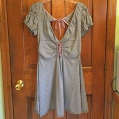 """Free People henna gray/purple corset ruffle dress Super cute gray and purple ruffled short sleeve lace up/corset henna dress by Free People. Only worn a few times and is in excellent condition with no rips, stains or tears. Haven't seen this style dress around in a long time since I got it a while back. Has a keyhole back with purple string tie. Very flattering cut! Size large. 60% cotton 40% polyester, very soft fabric. 33"""" length, 18"""" waist, and 15"""" waist with stretch. Feel free to ask…"""