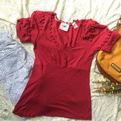 Red detailed Tee This is a pre-loved item. But in still good condition. There are details on the sleeves as well as the caller and buttons are all intact. This is a size medium but fits like a small. I am open to all offers. If any questions please not hesitate to ask.⭐️ Anthropologie Tops Tees - Short Sleeve