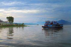 Niños viajando en el techo de un bote en Pangururan, Indonesia
