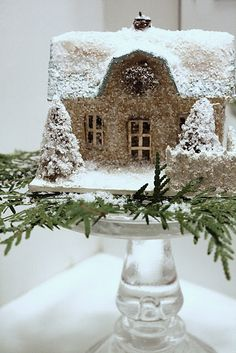 Cardboard homes set on cake stands as Christmas decor