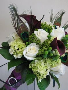Mini green hydrangea, white roses, hypericum berries, brixilla berries, eggplant calla lilies with peacock feathers make a striking Bridal bouquet. The Rhinestone feature on the ribbon makes an elegant statement.