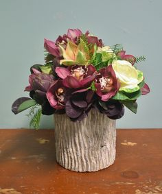 Burgundy, green, cream and deep purple make a lush arrangement in this bark textured ceramic container