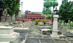 Rawalpindi, a view of the graves in the cemetery, with the building in the background: One such landmark is located on Murree road, tucked between the shops of the New Jewellery Market. No one would guess that between the ostentatious glittering shops and the din of traffic there is an old Zorastrian cemetery(Parsi). As one enters the compound, the serenity of the lush green grass and shady trees takes one by surprise. Rawalpindi's Parsi graveyard houses a number of graves and a colonial…