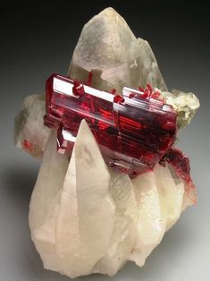 "Realgar (an arsenic sulfide mineral, also known as ""ruby sulphur"" or ""ruby of arsenic""):  ruby-red crystals in translucent Calcite scalenohedrons"
