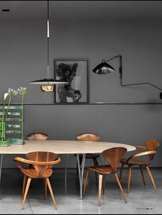Charcoal gray wall. creative lighting. mid-century modern table and chairs.