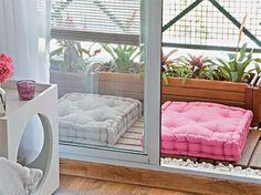 Para uma varanda muito pequena, vasos cumpridos de madeira economizam espaço, enquanto o deck e as pedras deixam com cara de jardim.