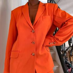 @sgturningpoint Orange oversized blazer with buttons, two front pockets and v-neck plunge. Structured shoulders and under bottom length. Designer brand, black influencer, Paris. www.sgturningpoint.com