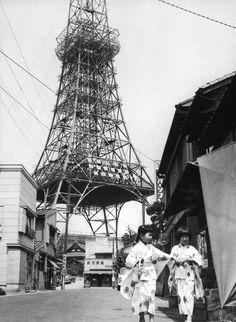 Two young girls in kimono in a street near the almost completed Tokyo Tower - July 1958 Source : Keystone