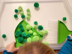 ⭐Montessori Inspired Practical Life Sweeping Pom Poms Activity⭐ St. Patricks Day Style with green pom poms and green broom and dust pan I picked up from the Dollar Tree. This activity is great for some added fun to normal sweeping and is great for hand eye coordination. #macntatersblog #macntaterstotschool #marchtotschool #totschool
