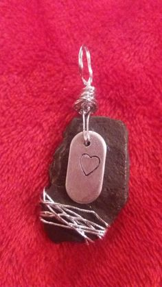Stamped heart on slate and wire wrapping.