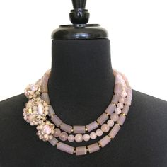 """Blush and Bashful--As any Southern Belle knows, the most complimentary pinks are always """"blush and bashful."""" (We promise to stop with the references and quotes there...though we could go on and on!)   Awash in your signature shades, faceted chalcedony cylinders (a rarity to find them in this natural hue) and polished rose quartz strands are adorned at the side by a matching brooch and earrings set from the 1950s or 60s.  Covered in sugar beads and glass jewels, the vintage baubles help…"""