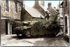 StuG III of Sturmgeschütz-Brigade 394 in rue Saint-Michel à Lonlay L'Abbaye, Normandy, June 1944. The town would be almost totally destroyed by heavy fighting over the next few days. (Colourised by Doug)