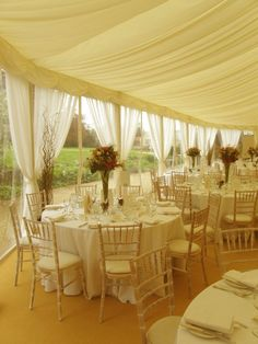 Charlton House Somerset   Muslin drapes on windows of a permanent marquee, twisted willow clusters and limed chiavari chairs with ivory seat pads by www.stressfreehire.com #venuetransformers