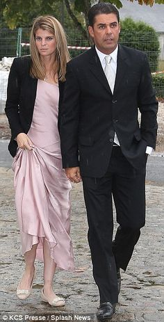 9-14-13.  Despite the inclement weather, Onassis appeared relaxed on the arm of husband Álvaro de Miranda Neto