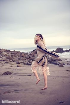Posing on the beach, Miley Cyrus wears knit sweater over sheer skirt