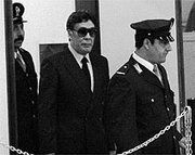 """Pizza Connection Trial - Turncoat witness Tommaso Buscetta (in sunglasses) is led into court at the """"Maxi Trial"""", circa 1986 ."""