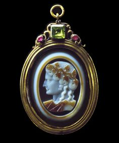 Sardonyx bust of a maenad, or possibly Ariadne, consort of Bacchus, head crowned with ivy , falling in ringlets to her shoulders, neckline draped, facing in profile towards the left. The border, ivy garland and robe in yellow-brown over white over brown layers within a bevelled border. In gold pendant, the frame with moulded edge surmounted by a chrysoprase between two rubies amidst scrolls. Cameo:1st century A.D., Pendant:c.1700.