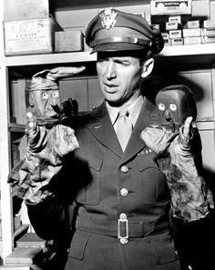 Visiting his hometown in 1945, Col. Jimmy Stewart plays with a pair of puppets he made when he was seven years old.