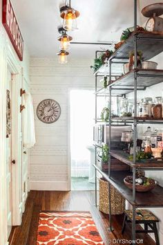 Floor-to-ceiling shelves give this space purpose and offer lots of room to stow pantry items and small appliances. New vintage-style ceiling lights brighten the formerly dark area.