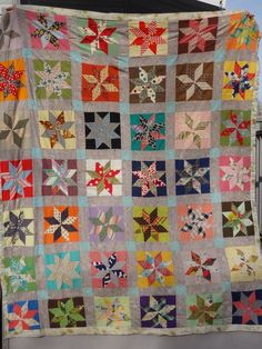 Vintage Quilt. Retro Lemoyne Star Quilt. Floral.    I like the colored backgrounds and the sashing. LeMoyne Star quilts tend to have the stars floating in a sea - or a sky - of white or a neutral solid - I like them contained in a square.