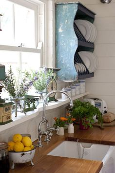 Love the book shelf thing with the dishes!    Wooden countertop, shelf rack, wide window sill acting as shelf