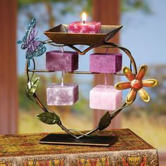 "This metal candle on rope holder features a yellow flower, green leaves and a purple and blue butterfly that decorate a heart-shaped wire. This heart provides a place for you to burn one candle, and showcase the other four that are part of each Candle on Rope. The ""featured"" candle will provide gentle illumination from its lofty perch on top of the heart, while the others hang gracefully, two by two, inside it."