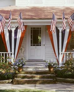 This porch displays red, white, and blue bunting (the fabric that flags are made from) that has been tacked to the eaves and tied with ribbon at the bottom. The trios of small flags are held up by aluminum brackets.