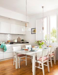 Cocina comedor en blanco con mesa rectangular y lámparas colgantes de cristal. Ventana con porticones 00429030