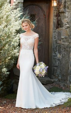 Turn heads in this off-the-shoulder wedding gown from Essense of Australia. With the option for the bodice to be lined or unlined, you can make this standout style as flirty as you'd like! The elegant lace of this Lace and Crepe gown extends from the bodice down the side of the skirt creating a unique, graphic pattern and elongating the body. The back of this gown is highlighted with an open, illusion back and breathtaking lace trim on the train. The back zips up beneath fabric buttons.