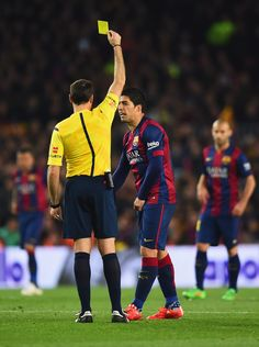 Referee Antonio Miguel Mateu Lahoz shows a yellow card to Luis Suarez of Barcelona during the La Liga match between FC Barcelona and Real Madrid CF at Camp Nou on March 22, 2015 in Barcelona, Catalonia.